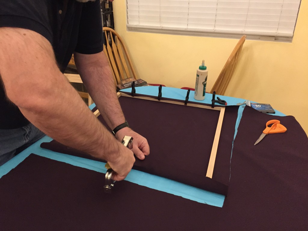Stapling the first side to the frame